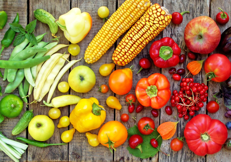 An array of fresh fruit and vegetables, including beans, peppers and apples
